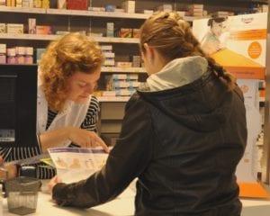 De apothekersassistente geeft uitleg aan de balie over de omzetting naar een biosimilar